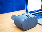 concept of virtual or augmented reality software development experience. developer workplace with VR goggles and laptop