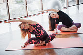 Concept of Yoga and Fitness Pregnancy. Portrait of a young model of pregnant yoga that is being developed indoors