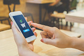 Concept online payment mobile technology. Hand of female using smartphone touching pay button mobile banking application in restaurant
