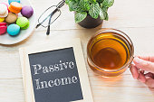 Concept Passive Income message on wood boards. Macaroons and glass Tea on table. Vintage tone.