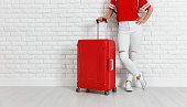 concept travel and tourism. legs of a girl with a red suitcase near  white empty brick wall