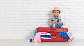 concept travel. a happy funny boy child with suitcase