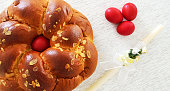 Traditional Easter bread ,tsoureki with a red egg in the middle , tree red eggs and an Easter candle beside