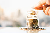 Man's hand holding coin to put in glass money jar with education label.