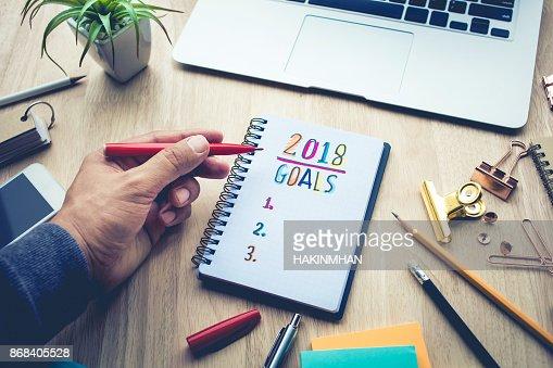 Notions de buts 2018 avec mâle main écrivant sur le bloc-notes : Photo