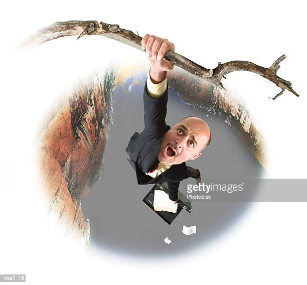 conceptual caricature of a caucasian business man in a suit as he hangs from a branch over a large canyon