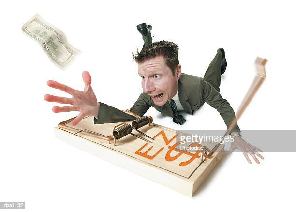 conceptual caricature of a caucasian business man in a suit as he gets his arm caught in a mouse trap