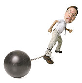 conceptual caricature of a caucasian man in a shirt and tie as he drags a big ball and chain around
