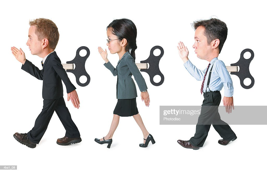conceptual caricature of a three business people with wind up cranks in the backs march forward in the same way : Stock Photo