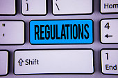 Conceptual hand writing showing Regulations. Business photo showcasing Rules Laws Corporate Standards Policies Security Statements written Key Button Keyboard with copy space. Top view.