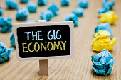 Conceptual hand writing showing The Gig Economy. Business photo text Market of Short-term contracts freelance work temporary poster board with blurry paper lobs laid serially mid yellow lob