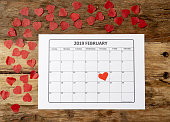 Conceptual image of 2019 february calendar and present gift wrapped with red ribbon on rustic vintage table in getting ready for saint Valentines day date, Love and romantic anniversary concept.