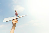 conceptual image of a little boy who dreams of flying on a paper airplane in the sky