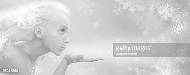 Conceptual image of winter goddess blowing cold snowflakes