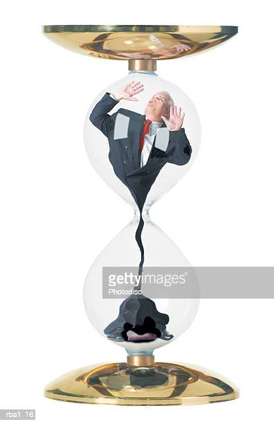 conceptual photo of a caucasian business man in a suit as he is stuck in and sucked through an hourglass