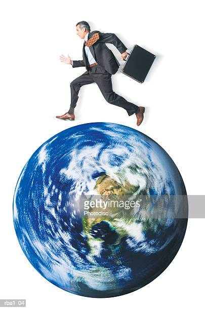conceptual photo of a caucasian man in a suit as he runs around and on top of the world