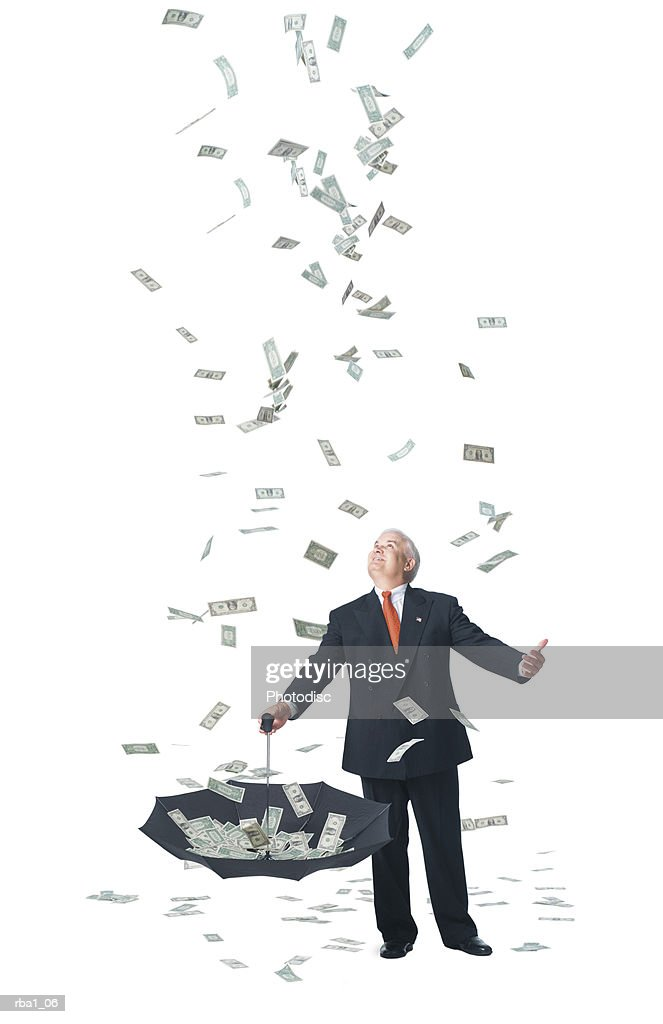 conceptual photo of a caucasian man in a suit standing in raining money and catches it in umbrella : Stock Photo