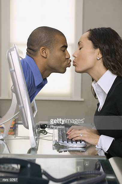 conceptual shot of a young adult woman who kisses a man coming out of her computer