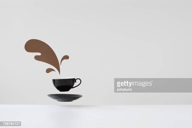 Conceptual spilled coffee from floating cup and saucer