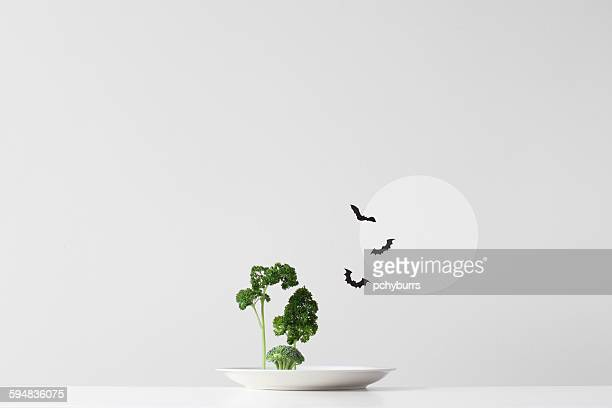 Conceptual spooky forest made up of green herbs and vegetables on a plate