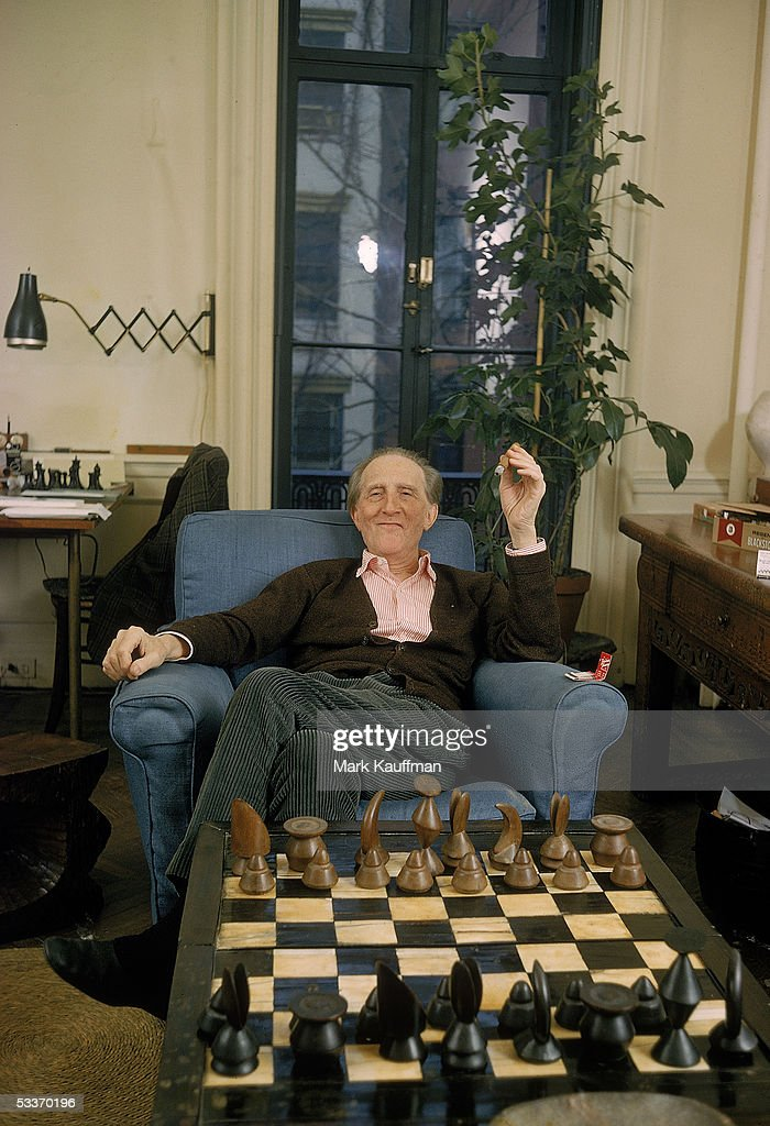 Conceptual surrealist artist Marcell Duchamp relaxing in his apartment behind a chessboard with pieces designed by fellow artist Max Ernst