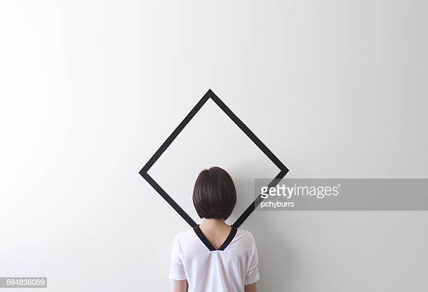 Conceptual woman camouflaged against a white wall