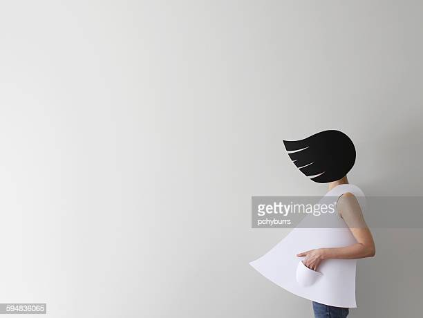 Conceptual woman wearing paper clothes and hair in wind