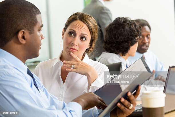 Concerned businesswoman reviewing sales figures with coworker during meeting