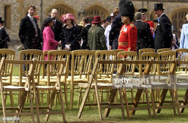 Concerned guests keep a safe distance as a swarm of bees encirle chairs on the lawn of Windsor CastleThe Queen was amused today when a rival swarm of...