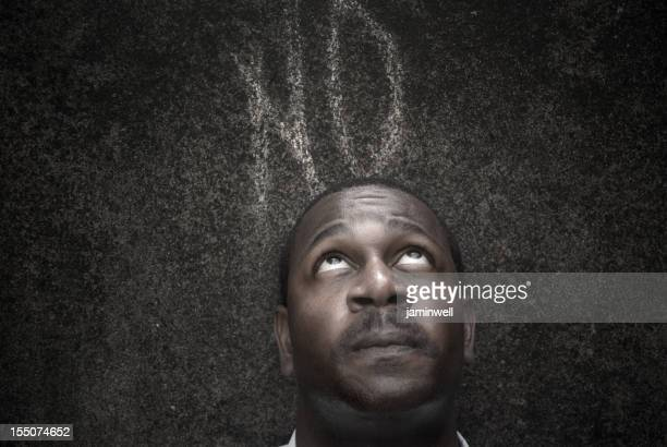concerned man against dark wall with word no