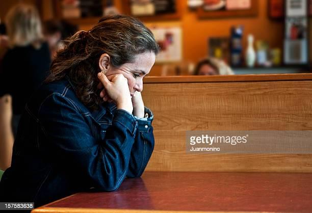 Preocupado mujer madura apoyarse su codos, en mesa de madera