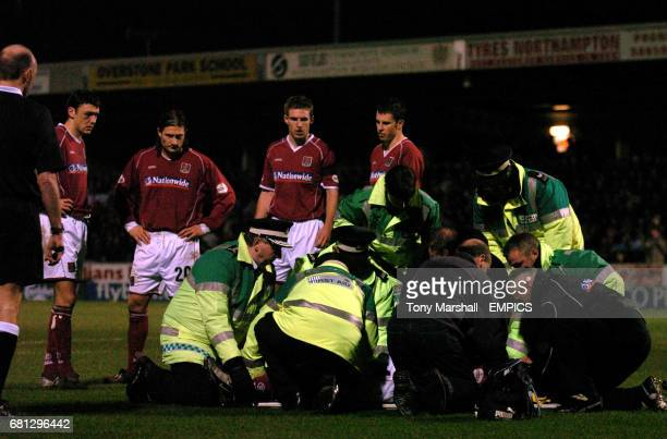 Concerned Northampton Town's players watch on as Chris Carruthers receives treatment before being stretchered off