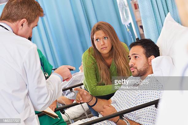 Concerned patient and spouse listening to doctor at hospital