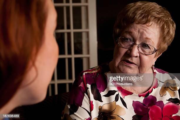 Besorgt Senior Erwachsenen zu ernsthaften Gespräch mit junge Frau