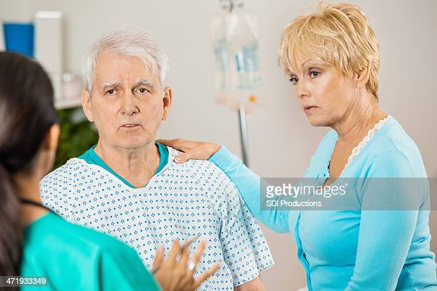 Concerned senior patient and spouse meeting with doctor in hospital