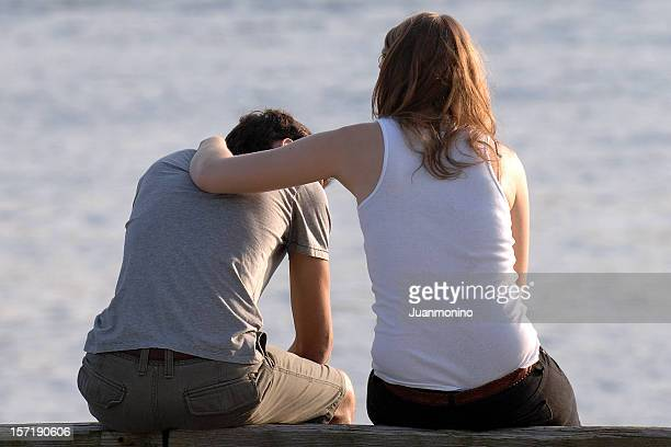 concerned woman comforts frustrated man at a beach
