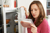 Concerned Woman Looking At Pre Packaged Meat
