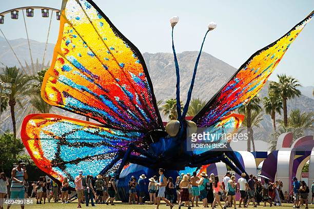 Concert attendees walk past a giant butterfly sculpture on the main grounds on day three of the Coachella Music Festival in Indio California on April...