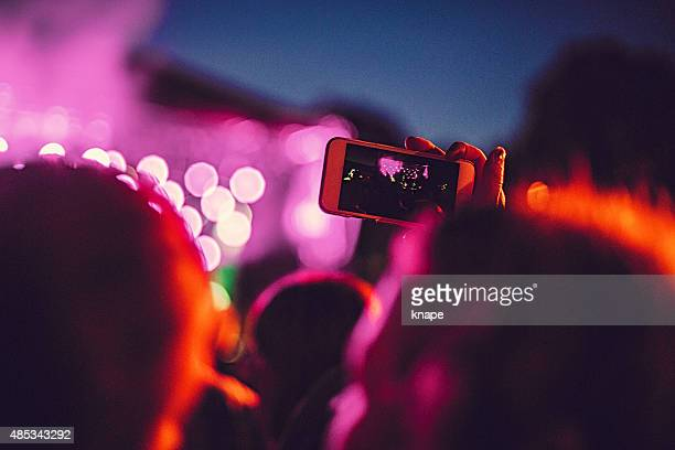 Concert audience taking pictures at music festival