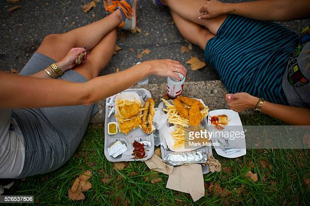 Concert goers enjoy a meal of chicken tenders and fries at the Budweiser Made in America Music Festival in Philadelphia PA on August 31 2013