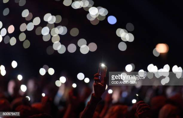 TOPSHOT Concert goers hold up their cellphones with torch lights switched on for peace as Tunisian singersongwriter Emel Mathlouthi performs on stage...