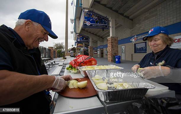 Concession vendors Phil Allan and Holly who declined to give her last name prepare a sack of onions for toppings and cookin in preparation for this...