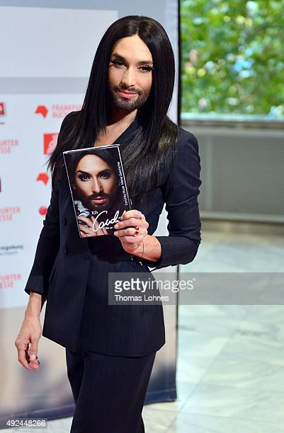 Conchita Wurst poses with his book at the red carpet before the opening ceremony of the 2015 Frankfurt Book Fair on October 13 2015 in Frankfurt am...