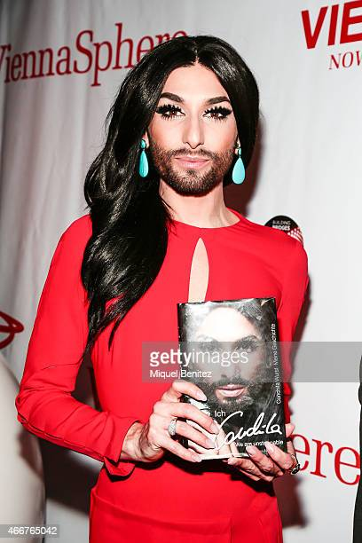Conchita Wurst poses with the book 'Conchita Wurst Maine Geschichte' 'Conchita Wurst My History' at the ViennaSphere at the Moll de la Fusta on March...