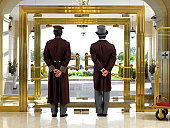 Concierge and bellboy standing at hotel entrance, rear view