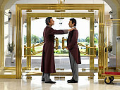 Concierge dusting bellboy's lapel in hotel foyer, side view