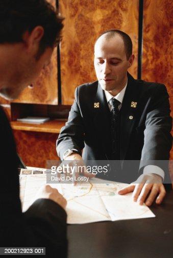 Concierge explaining at reception desk