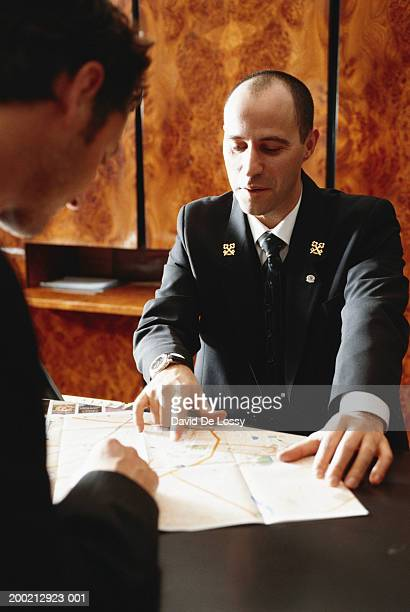 Concierge explaining at reception desk