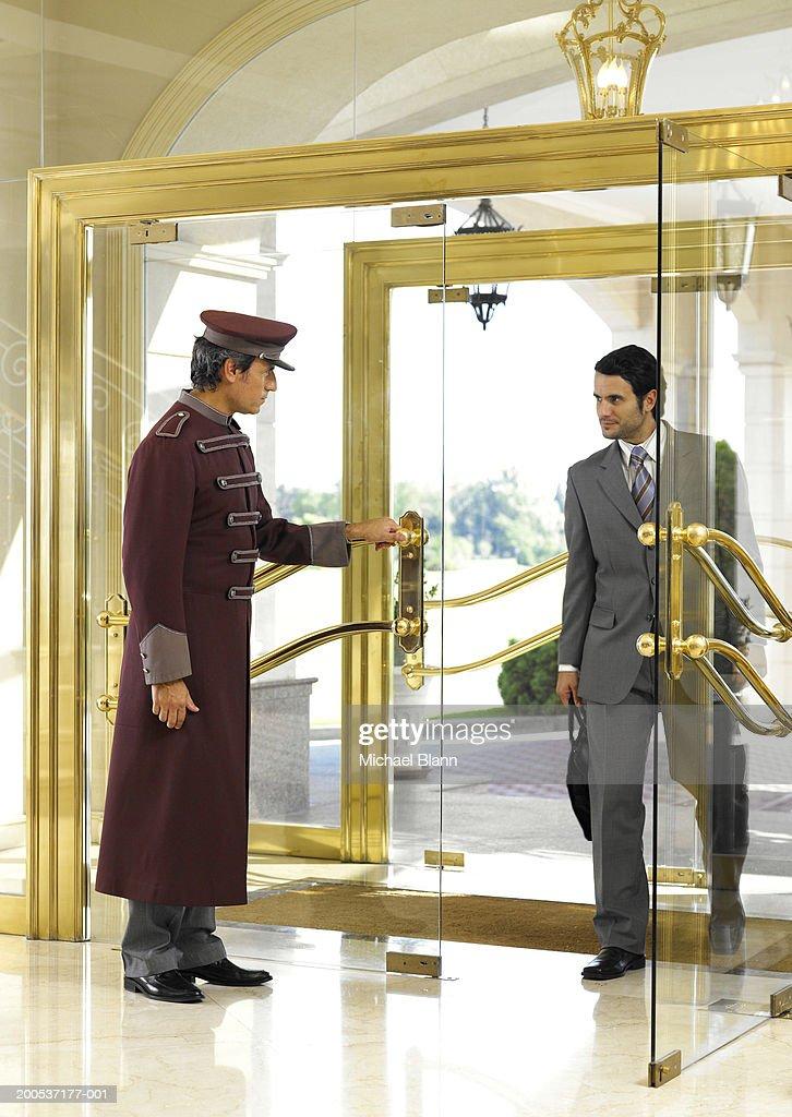 Concierge holding door open for businessman