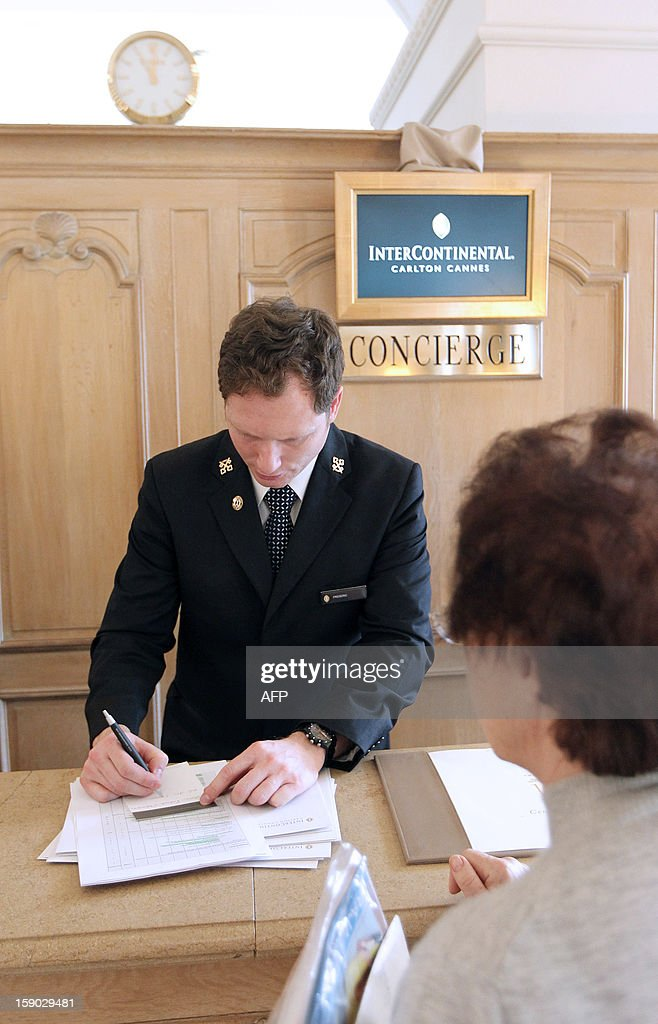 A concierge of the Intercontinental Carlton Hotel welcomes a customer at the reception desk of the hotel on January 4, 2013 in Cannes, southeastern France. AFP PHOTO / JEAN CHRISTOPHE MAGNENET